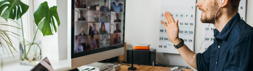 Young man having Zoom video call via a computer in the home office. Stay at home and work from home concept during Coronavirus pandemic.